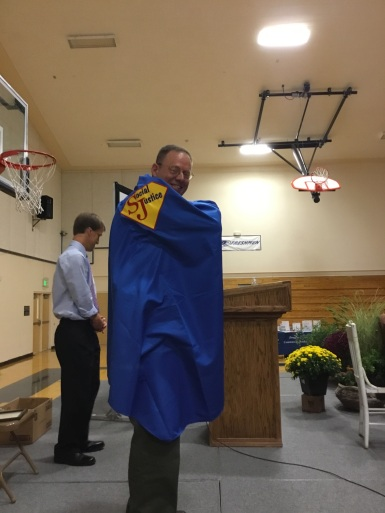 Lyon Co. Sheriff Al McNeil receives his Social Justice SuperHero cape